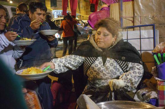 Un puesto callejero en La Paz sirve comida a varias personas.